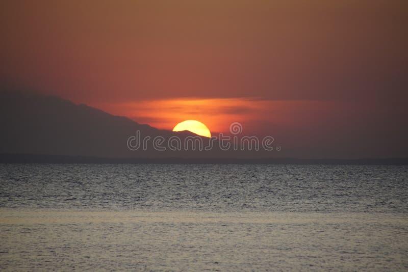 Crimson-Sonnenuntergang Ein ausgehender Berg am Horizont Meer und Abend Die Wolken stockbild