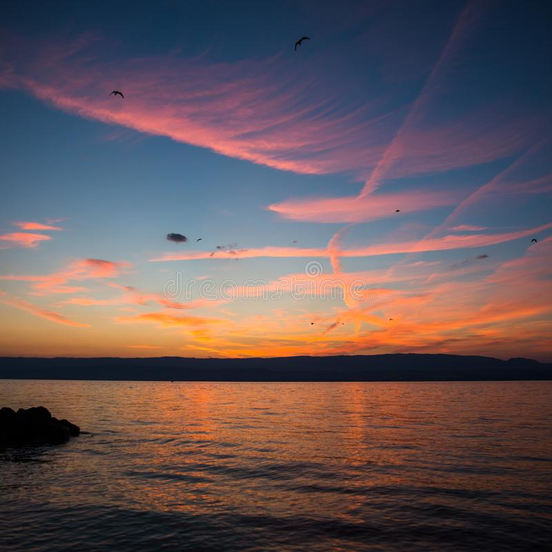 Crimson Sunset and Dramatic Sky over Lake Leman and Jura Mountains stock photo