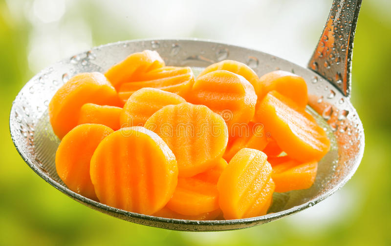 Crinkle cut sliced carrots in a kitchen ladle. Healthy boiled or steamed crinkle cut sliced farm fresh carrots in a kitchen ladle ready to be served as an stock photography