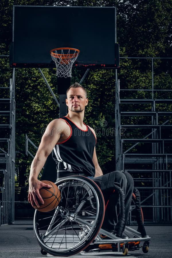Cripple basketball player in wheelchair holding ball. Cripple basketball player in wheelchair holding ball on open ground royalty free stock photography