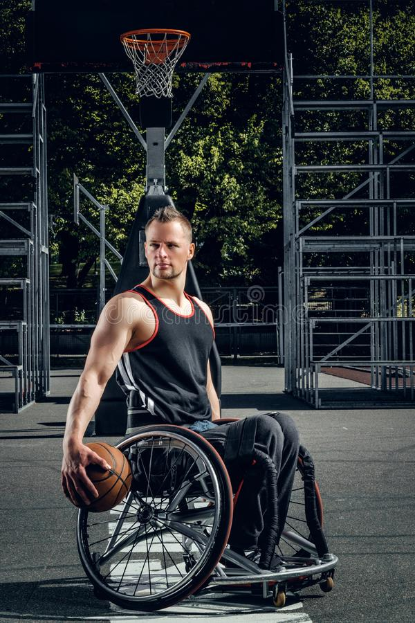 Cripple basketball player in wheelchair holding ball. Cripple basketball player in wheelchair holding ball on open ground stock images