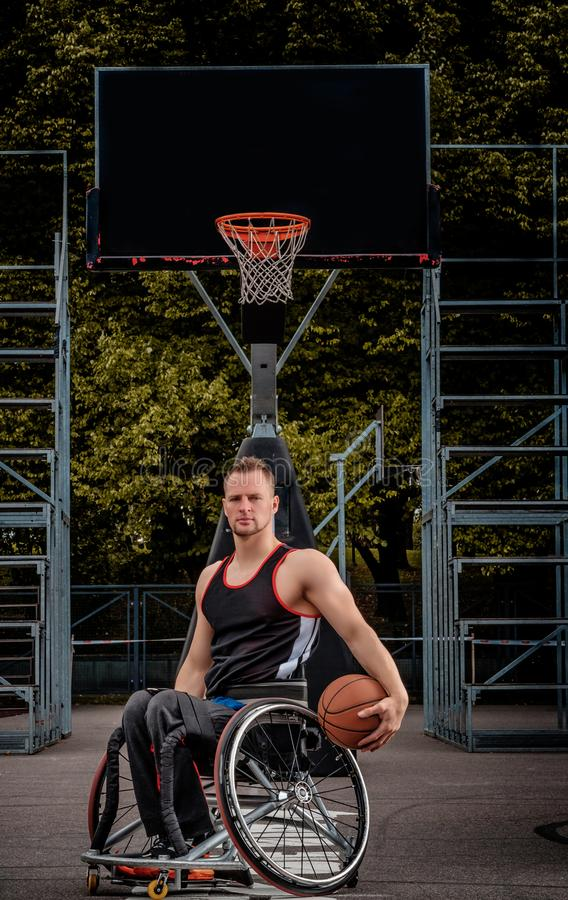 Cripple basketball player in a wheelchair holds a ball on an open gaming ground. Cripple basketball player in a wheelchair holds a ball on open gaming ground stock photos
