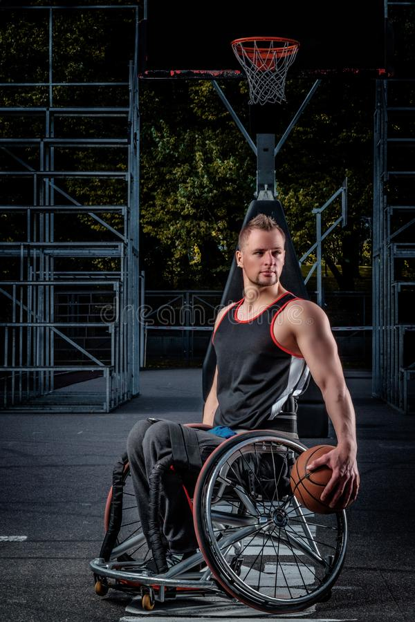 Cripple basketball player in a wheelchair holds a ball on an open gaming ground. Cripple basketball player in a wheelchair holds a ball on open gaming ground stock photo