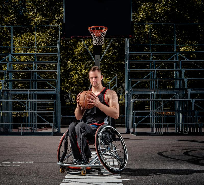 Cripple basketball player in a wheelchair holds a ball on an open gaming ground. Cripple basketball player in a wheelchair holds a ball on open gaming ground stock photography