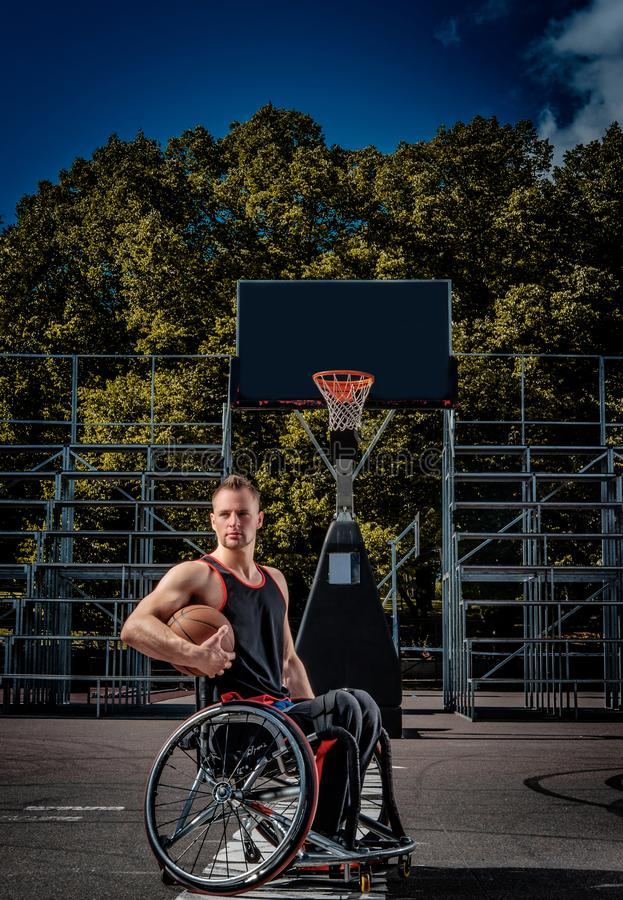 Cripple basketball player in a wheelchair holds a ball on an open gaming ground. Cripple basketball player in a wheelchair holds a ball on open gaming ground royalty free stock photo