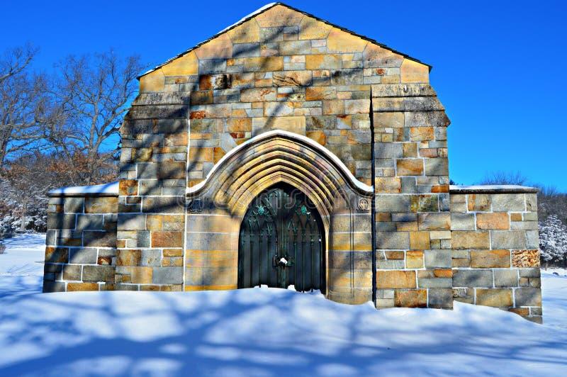 Cripta de pedra no cemitério nevado imagens de stock