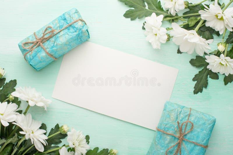 Crisântemos brancos com presentes em um fundo de madeira, com espaço vazio para a escrita ou a propaganda foto de stock royalty free
