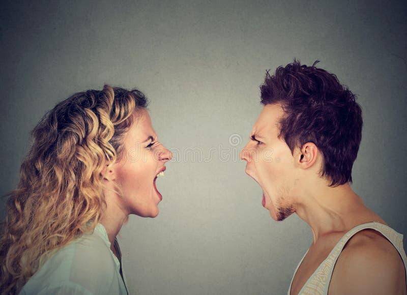 Cris fâchés de couples face à face images stock