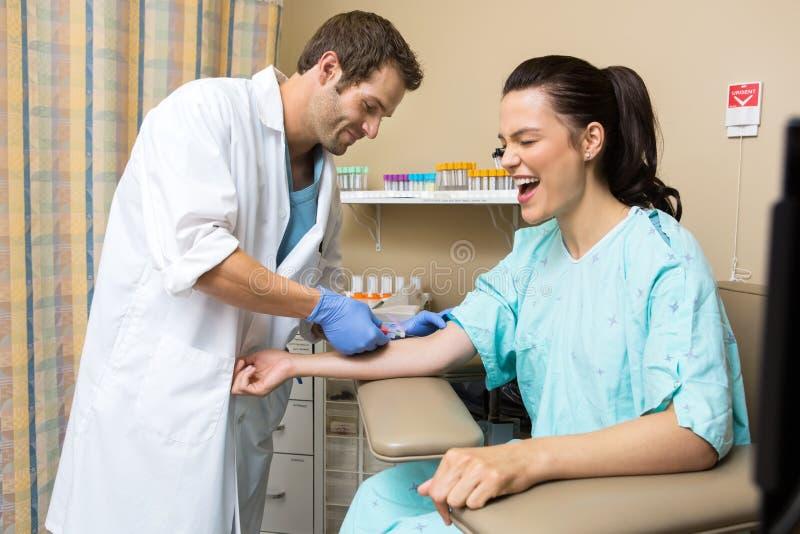 Cris patients tandis que docteur Drawing Blood images libres de droits