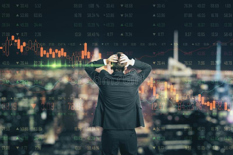 Crisis concept with businessman in a panic and forex chart screen with graphs going down royalty free stock photo
