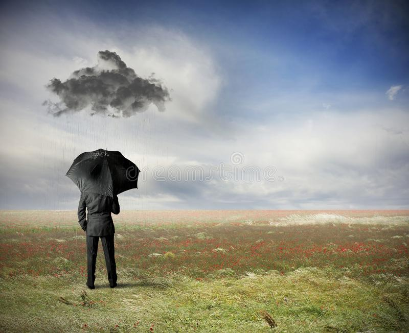 Crisis. Concept with businessman under a black cloud royalty free stock photography