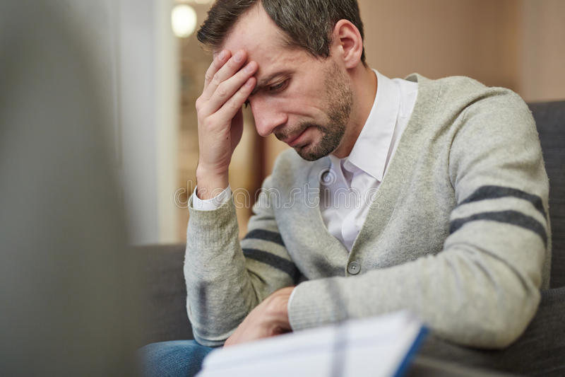 Crisis in life. Unhappy man visiting his counselor stock photo