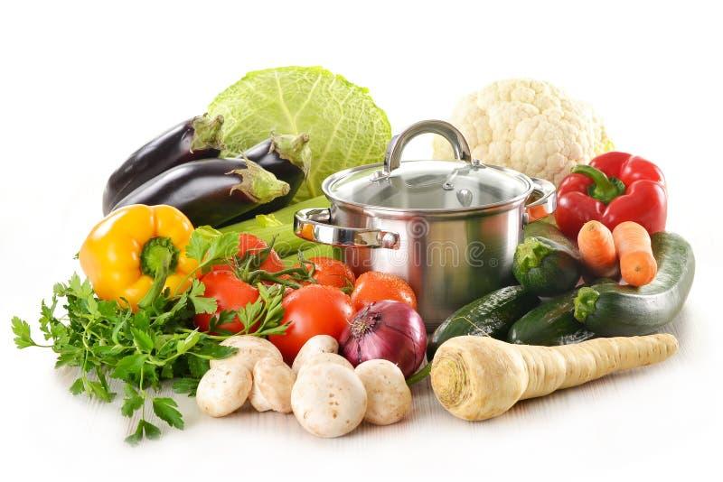 Crisol y verduras frescas aislados en blanco foto de archivo