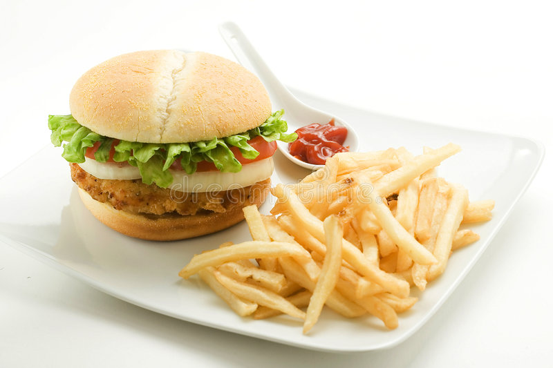 Crisp chicken burger tomato onion cheese lettuce. Crisp chicken burger with tomato onion cheese lettuce isolated royalty free stock photography
