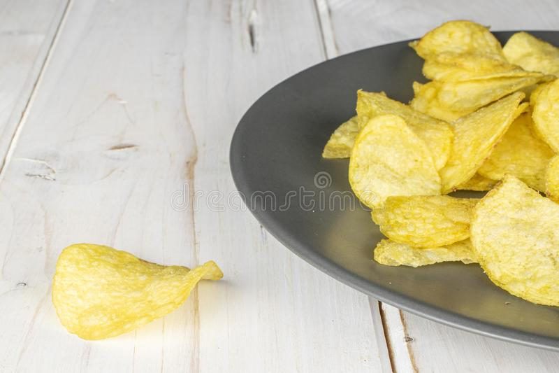Crisp potato chip on grey wood stock image