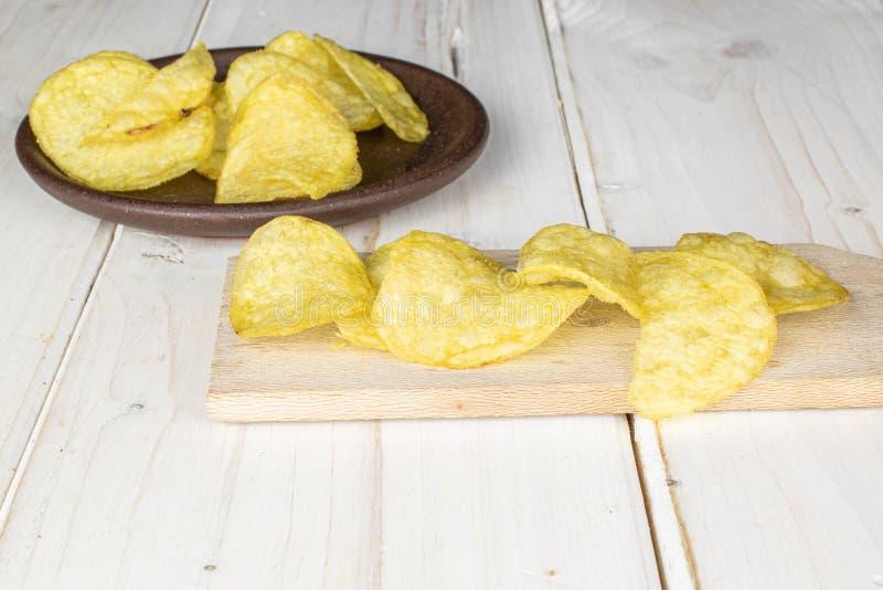 Crisp potato chip on grey wood stock images