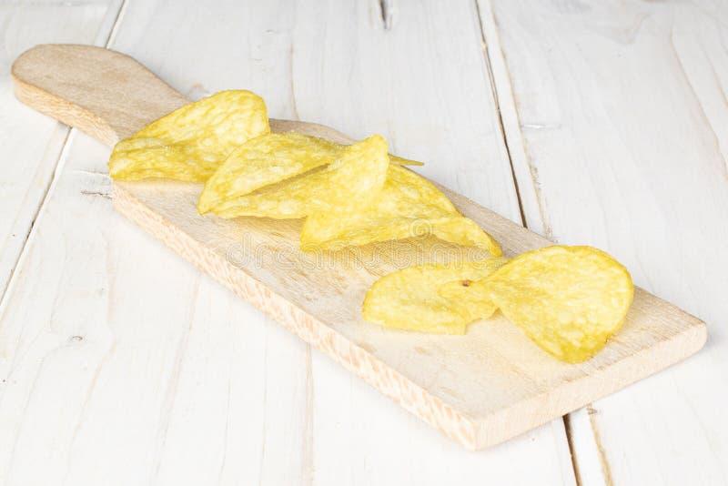 Crisp potato chip on grey wood royalty free stock photos