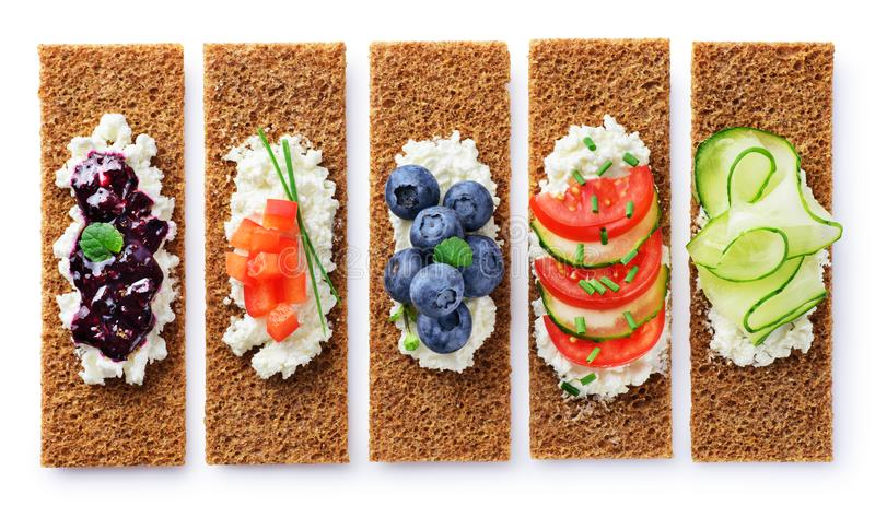 Crispbread with cheese, vegetables, jam and berries stock photo