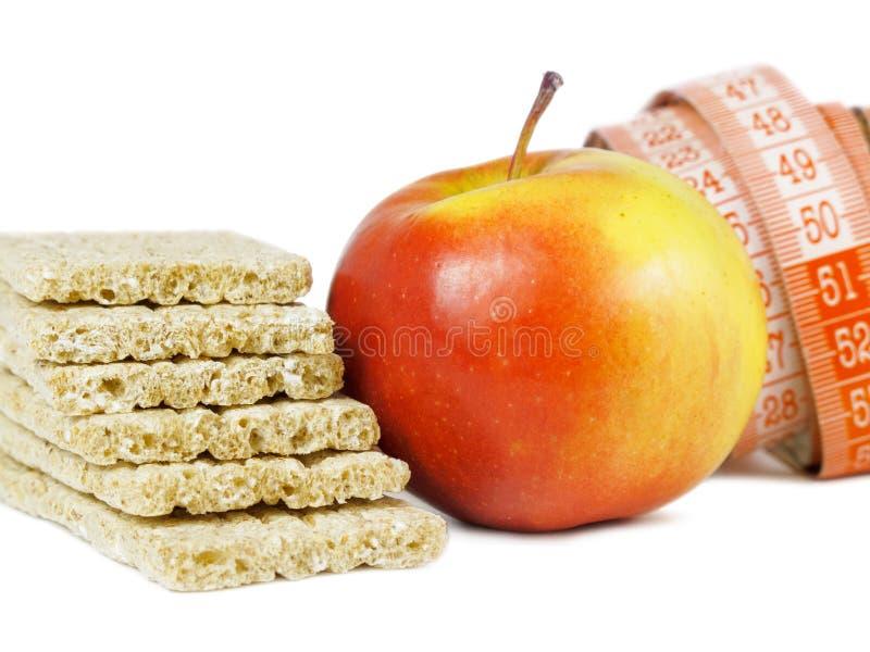 Crispbread, czerwony jabłko i pomiarowa taśma jako pojęcie zdrowa dieta, fotografia royalty free