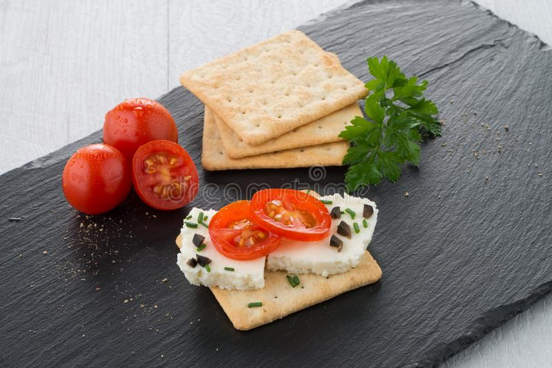 Crispbread with fromage. Tomato and olives on black ardoise tray royalty free stock photography