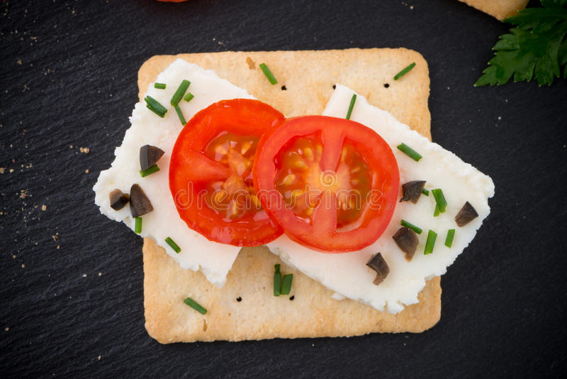 Crispbread with fromage. Tomato and olives on black ardoise tray royalty free stock photos