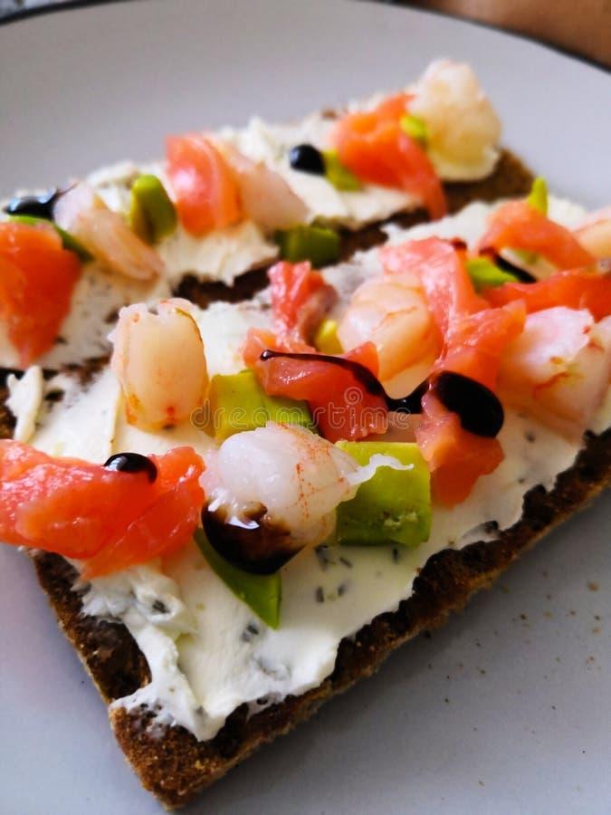 crispbread pan con queso del aguacate y camarón y bocadillo rojo de los pescados con los pescados y el aguacate rojos imágenes de archivo libres de regalías