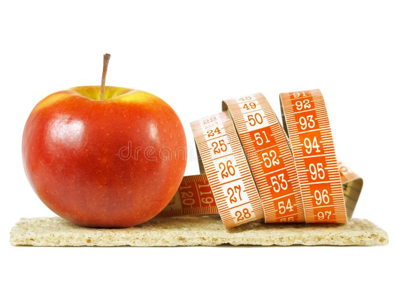 Crispbread stack, red apple, measurement tape as concept of healthy diet stock photography