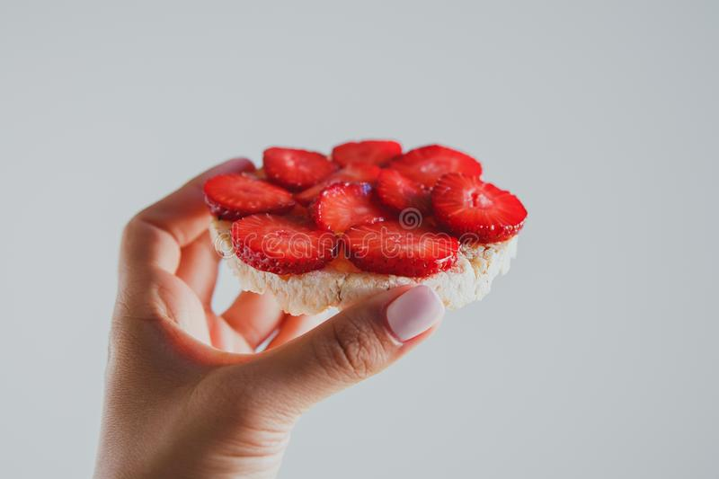 Crispbread with strawberries in hand on a gray background royalty free stock photo