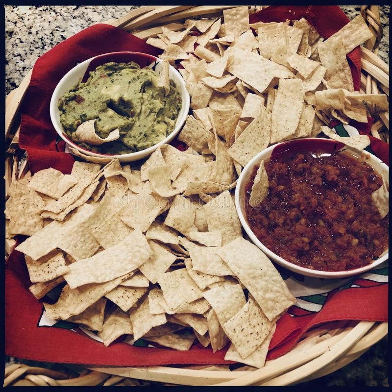 Crisps with guacamole and salsa stock images