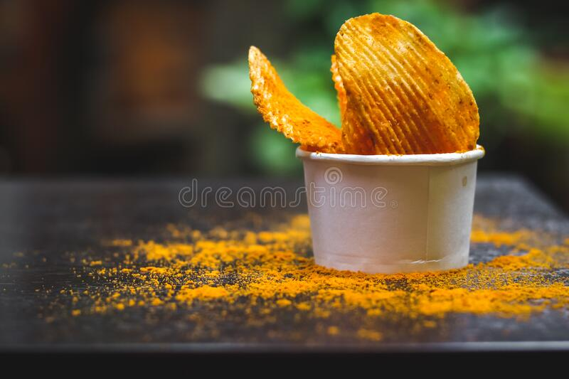 Crisps Hot and Spicy Potato Chips ready to eat on the table with green plant background. Image royalty free stock photos
