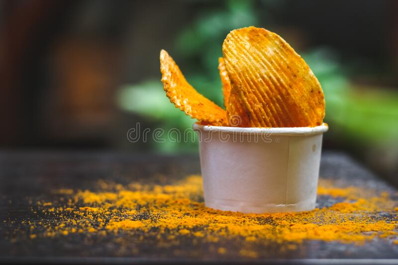 Crisps Hot and Spicy Potato Chips ready to eat on the table with green plant background. Photo stock photo