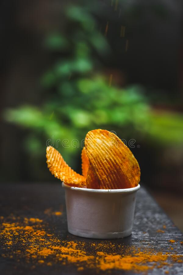 Crisps Hot and Spicy Potato Chips ready to eat on the table with green plant background. Shot royalty free stock images