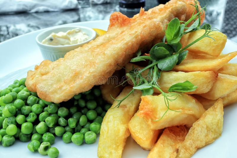 Traditional english food fish and chips with green peas. Crispy battered fish and chunky potato chips served with boiled green peas and mayonnaise, traditional royalty free stock photography