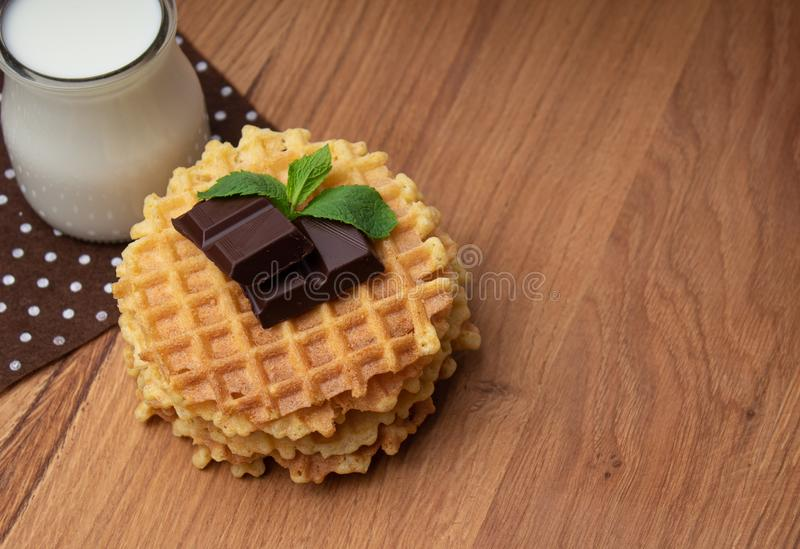 Crispy Belgian waffles with chocolate chips. A small glass cup with milk on a brown polka dot napkin stock photos