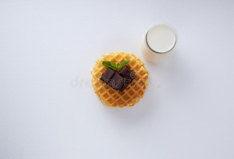 Crispy Belgian waffles with chocolate chips on a white textured surface. Small glass jug with milk stock images