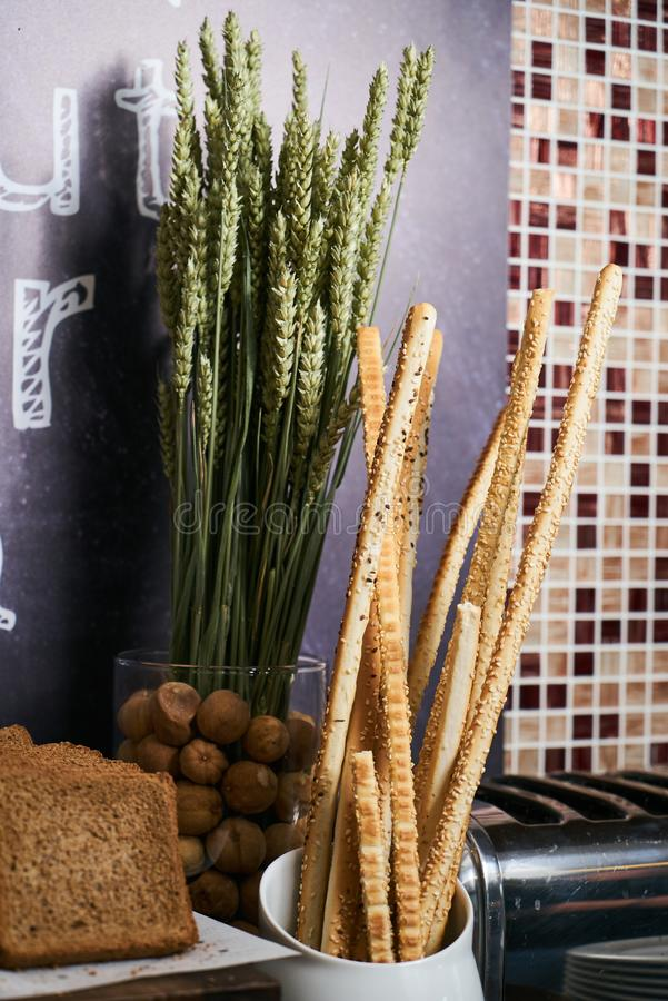 Crispy bread sticks and wheat sprouts on dark slate background w. Ith copy space. Traditional Italian snack, bread - grissini, close-up royalty free stock image