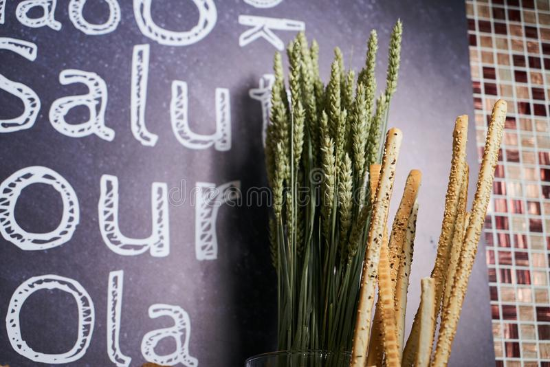Crispy bread sticks and wheat sprouts on dark slate background w. Ith copy space. Traditional Italian snack, bread - grissini, close-up stock image