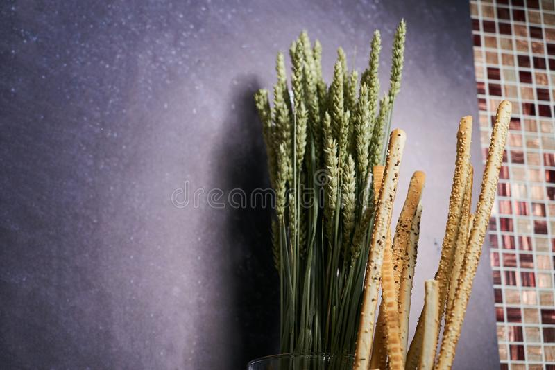 Crispy bread sticks and wheat sprouts on dark slate background w. Ith copy space. Traditional Italian snack, bread - grissini, close-up stock photo