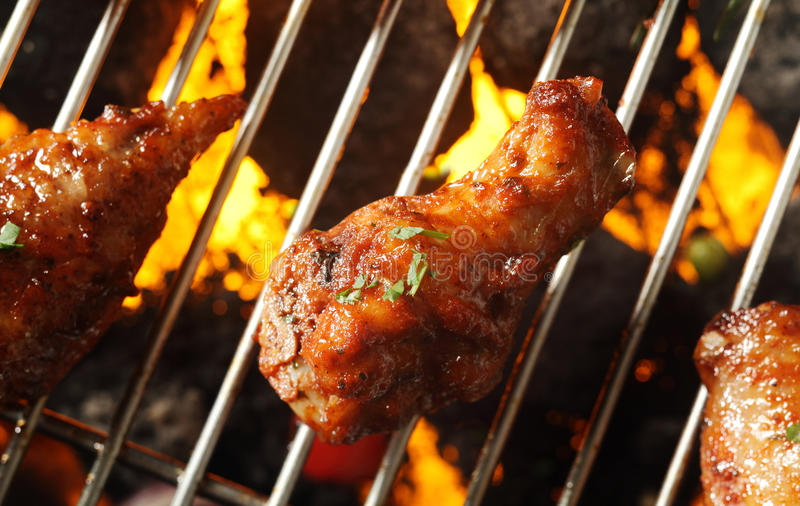 Crispy brown chicken legs on a barbecue stock image