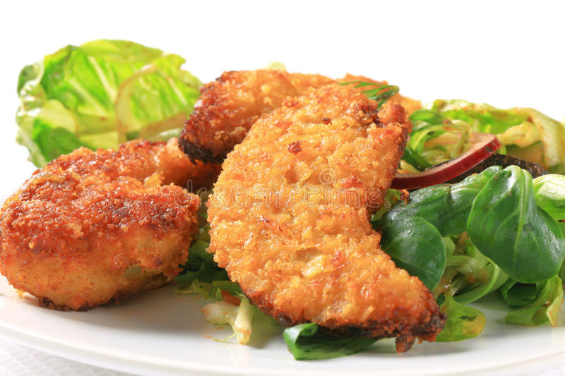 Crispy chicken tenders. With salad greens stock image