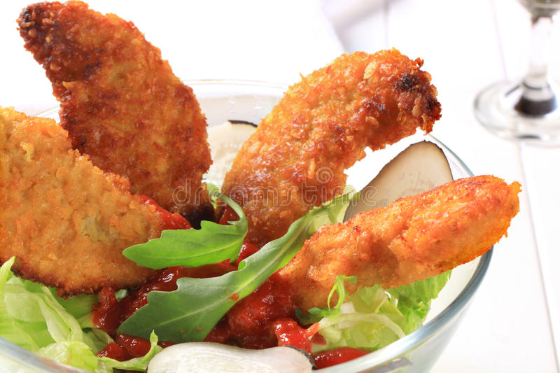 Crispy chicken tenders with salad. Crispy chicken tenders with tomato dipping sauce and lettuce royalty free stock photo