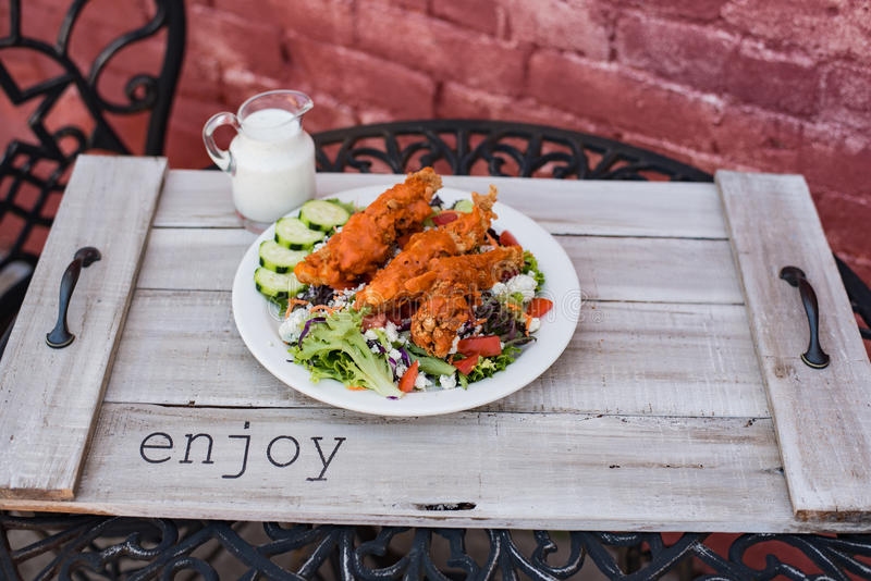 Crispy chicken tenders on a salad stock images