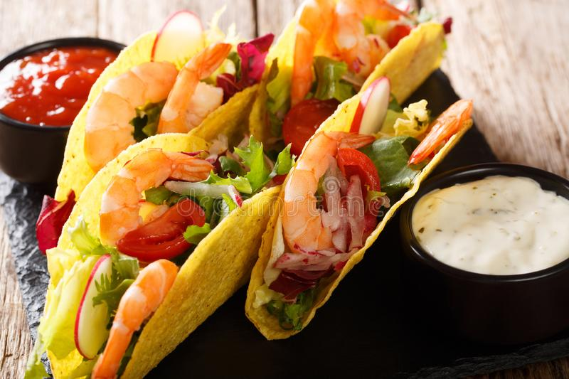 Crispy corn tacos with seafood fresh vegetables and sauces close-up. horizontal stock image