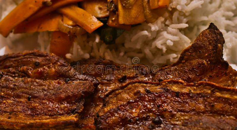 Crispy dark brown roasted pork belly seasoned with coarse ground pepper, on white rice with carrot sticks stock image