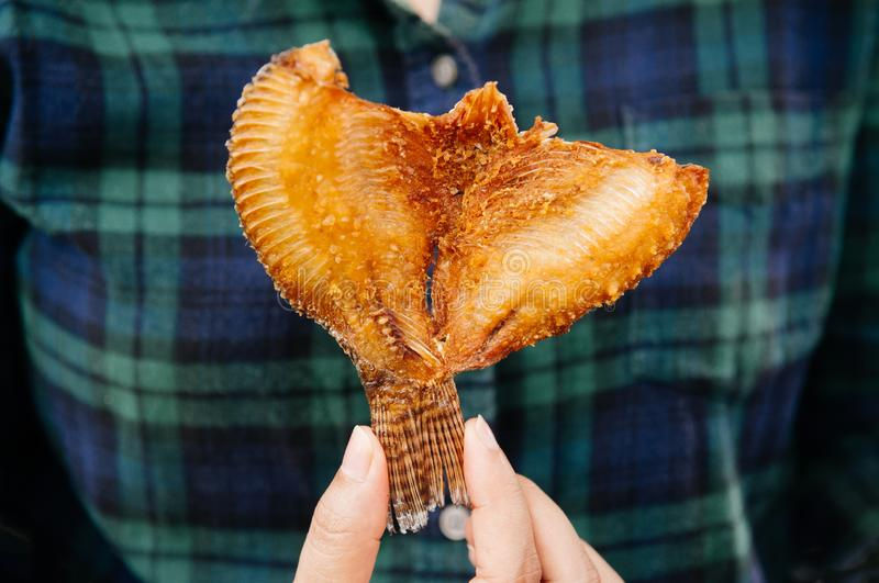 Crispy deep fried fish in woman hand royalty free stock images