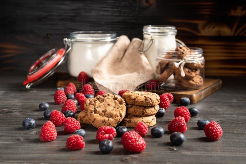 Crispy domowej roboty czekoladowi ciastka, malinki i czarne jagody, obrazy royalty free