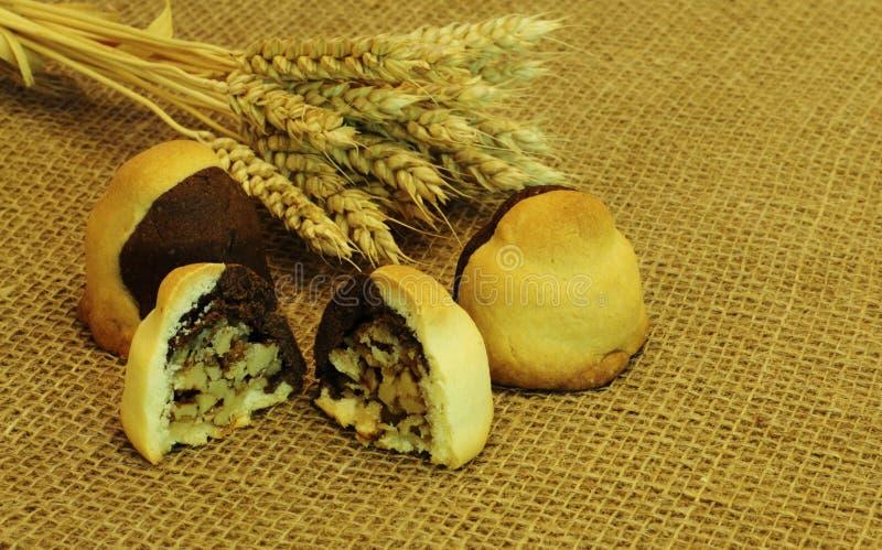 Crispy domowej roboty wyśmienicie podlewań ciastka faszerowali z orzechami włoskimi i pszenicznymi ucho na szorstkiej samodziałow zdjęcie royalty free