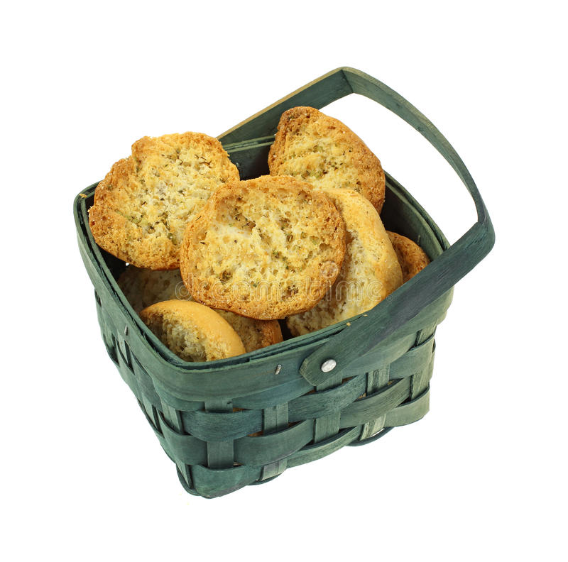 Crispy Dried Bread Slices in Basket. A green basket full of small toasted seasoned bread slices royalty free stock photos