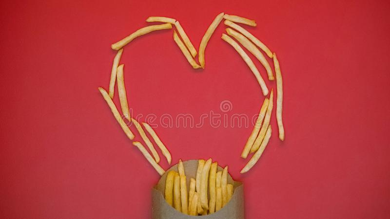 Crispy french fries heart shape symbol on red background, fast food, charity royalty free stock images