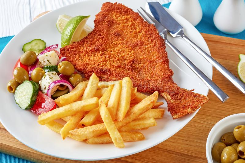 Crispy fried flounder in a breadcrumbs. Crispy fried flounder in breadcrumbs served with fresh vegetables, feta, olives greek salad and french fries on a white royalty free stock photos